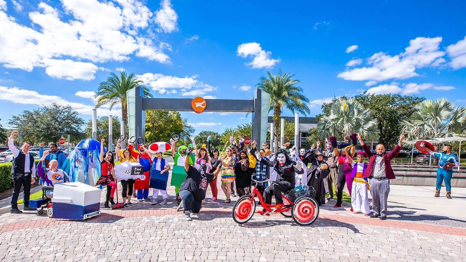 Staff and faculty posing under the Full Sail archway, wearing their Halloween costumes